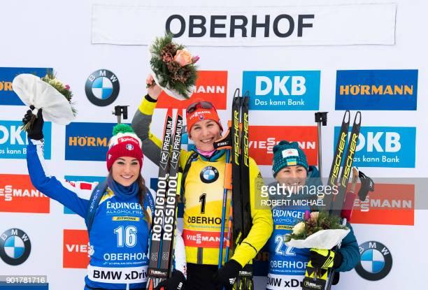 Second placed Dorothea Wierer of Italy winner Anastasiya Kuzmina of Slovakia and third placed Vita Semerenko of Ukraine celebrate on the podium after...