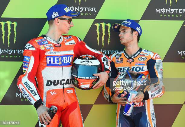 Second placed Ducati Team's Spanish rider Jorge Lorenzo talks to winner of the pole position Repsol Honda Team's Spanish rider Dani Pedrosa after the...