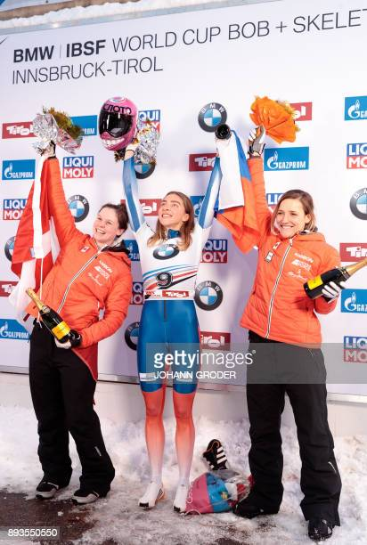 Second placed Elisabeth Vathje of Canada winner Elena Nikitina of Russia and third placed Mirela Rahneva of Canada celebrate on the podium after...