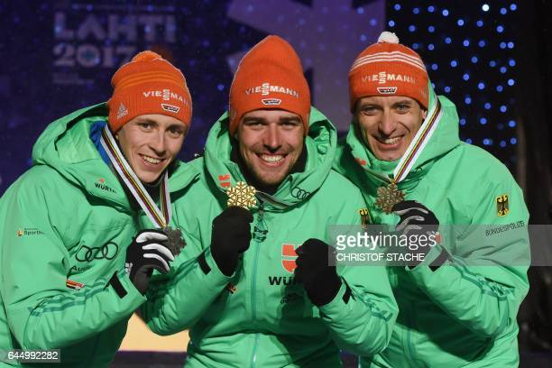Second placed Eric Frenzel winner Johannes Rydzek and third placed Bjoern Kircheisen of Germany celebrate during the medals ceremony for men's nordic...