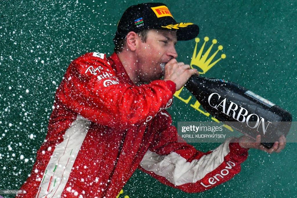 TOPSHOT - Second placed Ferrari's Finnish driver Kimi Raikkonen celebrates on the podium of the Formula One Azerbaijan Grand Prix at the Baku City Circuit in Baku on April 29, 2018.
