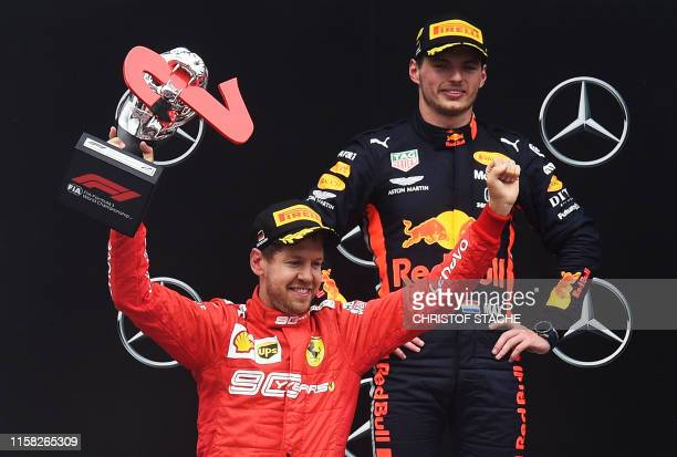 TOPSHOT Second placed Ferrari's German driver Sebastian Vettel and winner Red Bull's Dutch driver Max Verstappen celebrate on the podium after the...