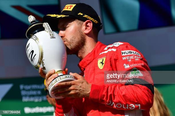 Second placed Ferrari's German Driver Sebastian Vettel kisses his trophy after the Formula One Hungarian Grand Prix at the Hungaroring circuit in...