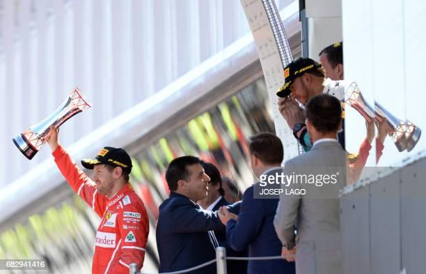 Second placed Ferrari's German driver Sebastian Vettel raises his trophy beside winner Mercedes' British driver Lewis Hamilton as they celebrate on...