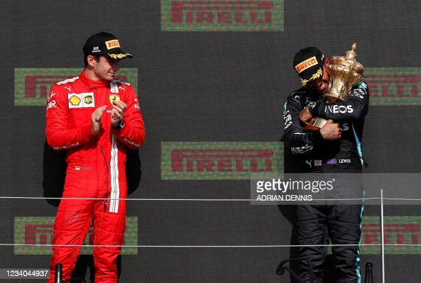 Second placed Ferrari's Monegasque driver Charles Leclerc watches as winner Mercedes' British driver Lewis Hamilton holds the trophy on the podium...
