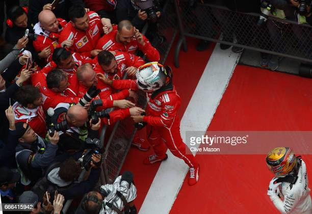 Second placed finisher Sebastian Vettel of Germany and Ferrari celebrates with his team as race winner Lewis Hamilton of Great Britain and Mercedes...
