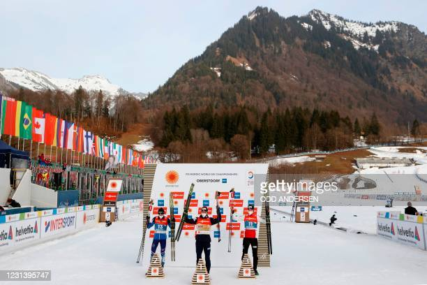Second placed Finland's Ilkka Herola, winner Norway's Jarl Magnus Riiber and third placed Norway's Jens Luraas Oftebro celebrate on the podium after...