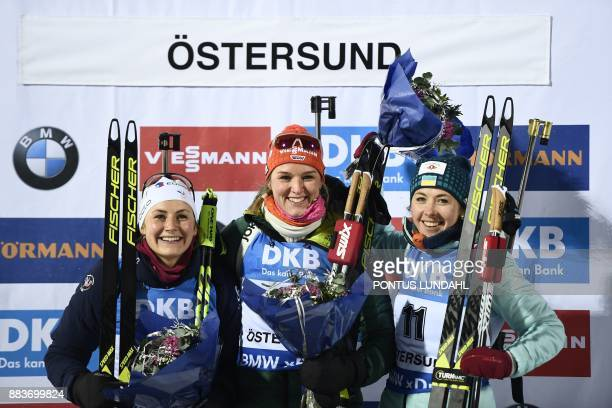 Second placed France's Justine Braisaz winner Germany's Denise Herrmann and third placed Ukraine's Yuliia Dzhima celebrate after the women 75 km...