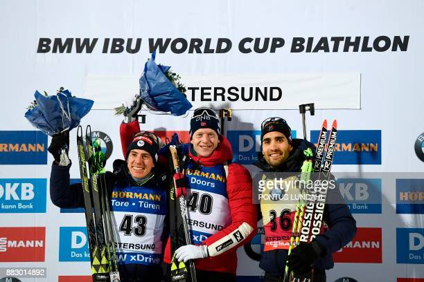 Second placed France's Quentin Fillon Maillet winner Norway's Johannes Thingnes Boe and third placed France's Martin Fourcade pose after the men 20...