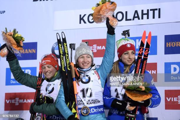 Second placed Franziska Hildebrand of Germany winner Darya Domracheva of Belarus and third Lisa Vittozzi of Italy celebrate on the podium after the...