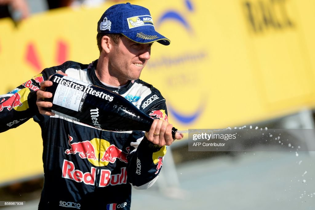 Second placed French driver Sebastien Ogier celebrates on the podium of the 53th Rally of Catalonia in Salou near Tarragona on October 8, 2017. Britain's Kris Meeke bagged his second win of the season at the Rally of Catalonia as France's Sebastian Ogier took a big step towards a fifth straight world title. / AFP PHOTO / Josep LAGO