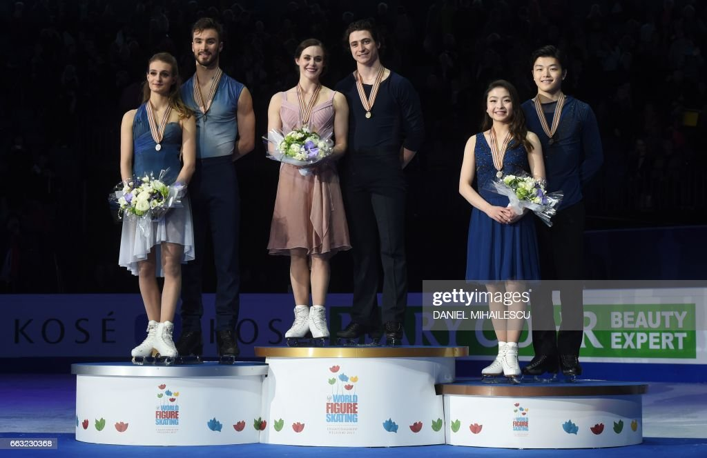 Second placed Gabriella Papadakis and Guillaume Cizeron of France, winners Tessa Virtue and Scott Moir of Canada and third placed Maia Shibutani and Alex Shibutani of the US stand on the podium after the Ice Dance / Free Dance event at the ISU World Figure Skating Championships in Helsinki, Finland on April 1, 2017. / AFP PHOTO / Daniel MIHAILESCU
