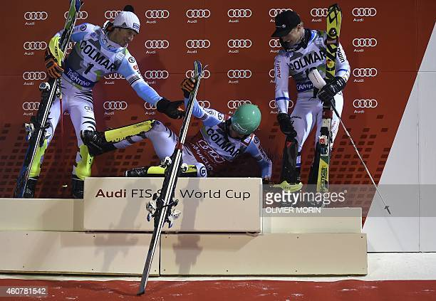 Second placed Germany's Fritz Dopfer and third placed Sweden's Jens Byggmark assists first placed Germany's Felix Neureuther onto the podium after...