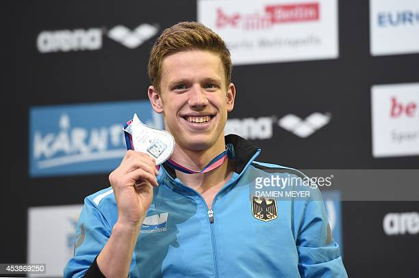 Second placed Germany's Philip Heintz celebrates with his medal on the podium after the men's 200m Medley final of the 32nd LEN European Swimming...