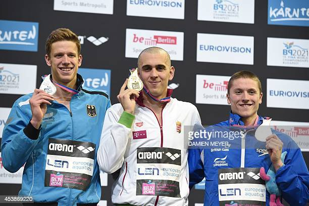 Second placed Germany's Philip Heintz gold winner Hungary's Laszlo Cseh and third placed Britain's Roberto Pavoni celebrate with their medals on the...