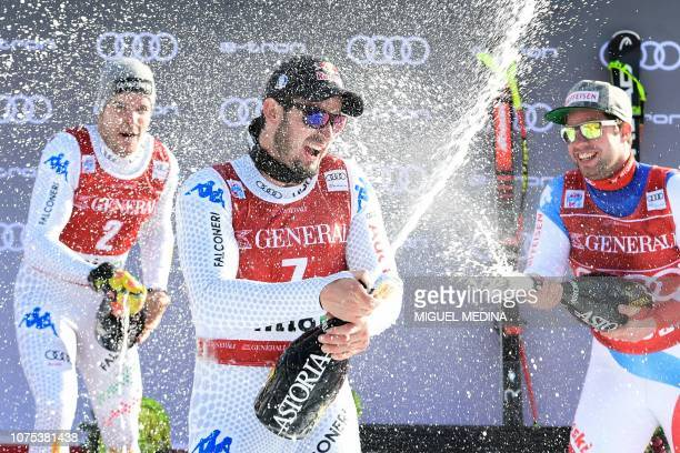 Second placed Italy's Christof Innerhofer winnner Italy's Dominik Paris and third placed Switzerland's Beat Feuz spray sparkling wine after the...