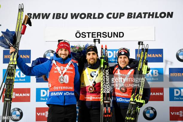 Second placed Jakov Fak of Slovenia winner Martin Fourcade of France and third placed Quentin Fillon Maillet of France celebrate after the men's 125...