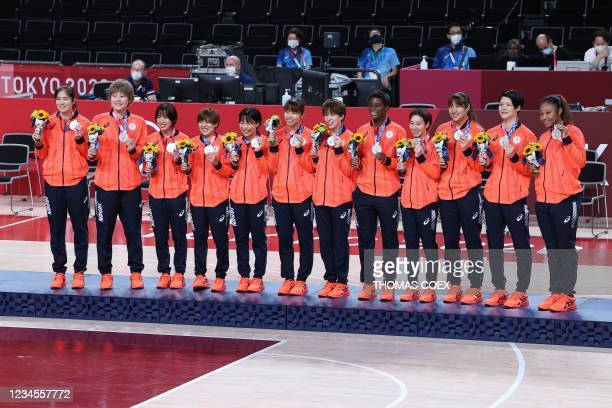 Second placed Japanese players pose for pictures with their silver medals during the medal ceremony for the women's basketball competition of the...