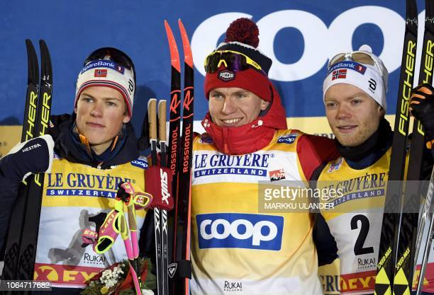 Second placed Johannes Hoesflot Klaebo of Norway winner Alexander Bolshunov of Russia and third placed Eirik Brandsdal of Norway pose after the Men's...