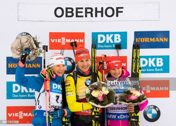 Second placed Kaisa Makarainen of Finland winner Anastasiya Kuzmina of Slovakia and third placed Veronika Vitkova of Czech stand on the podium after...