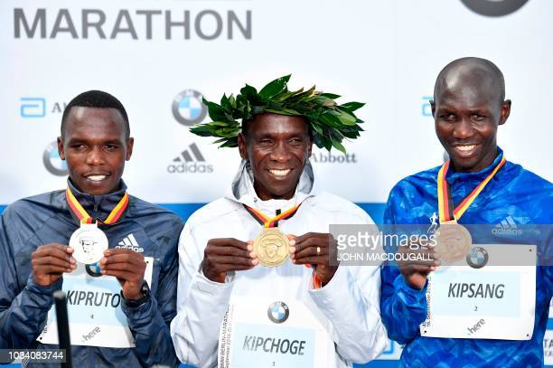 Second placed Kenya's Amos Kipruto winner Kenya's Eliud Kipchoge and third placed Kenya's Wilson Kipsang pose on the podium with their medals during...