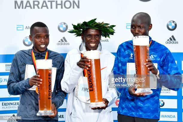 Second placed Kenya's Amos Kipruto winner Kenya's Eliud Kipchoge and third placed Kenya's Wilson Kipsang pose on the podium with beer during the...