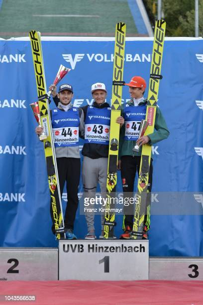 Second placed Killian Peier of Switzerland first placed Daniel Huber of Austria and third place Karl Geiger of Germany pose on the podium after the...