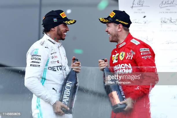 Second placed Lewis Hamilton of Great Britain and Mercedes GP and third placed Sebastian Vettel of Germany and Ferrari celebrate on the podium during...