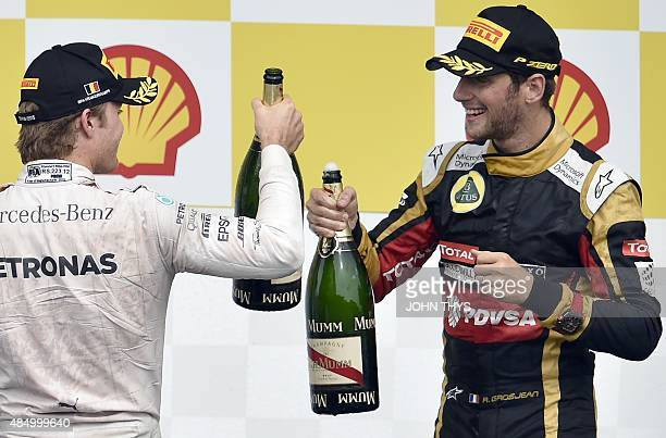 Second placed Mercedes AMG Petronas F1 Team's German driver Nico Rosberg and third placed Lotus F1 Team's French driver Romain Grosjean celebrate...