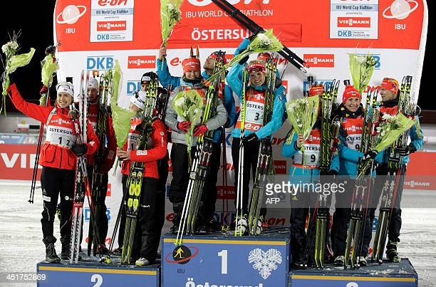 Second placed Norway mixed relay team Synnöve Solemdal Vetje Sjastad Christiansen Tora Berger and Tarjei Boe the Czech mixed relay team and winners...
