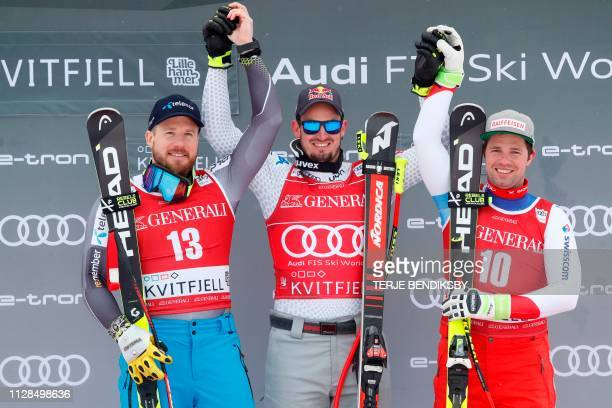 Second placed Norway's Kjetil Jansrud, first placed Italy's Dominik Paris and third placed Switzerland's Beat Feuz celbrate on the podium after the...