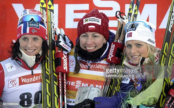 Second placed Norway's Marit Bjoergen winner Poland's Justyna Kowalczyk and second placed Norway's Therese Johaug pose on the podium during ladies 5...