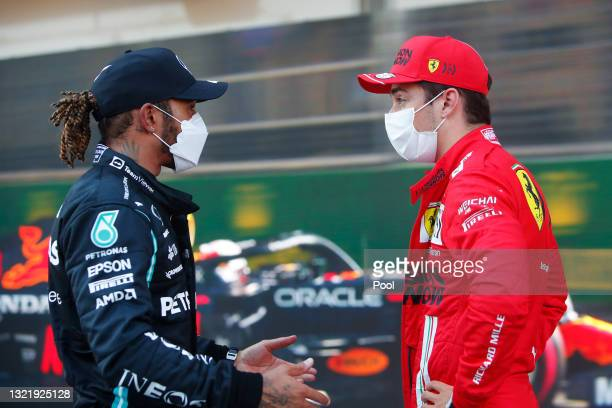 Second placed qualifier Lewis Hamilton of Great Britain and Mercedes GP talks with pole position qualifier Charles Leclerc of Monaco and Ferrari in...
