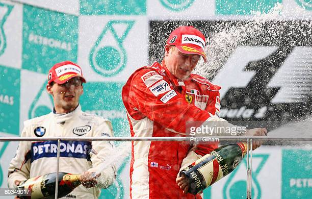 Second placed Robert Kubica of Poland and BMW Sauber celebrates on the podium with race winner Kimi Raikkonen of Finland and Ferrari in the Malaysian...