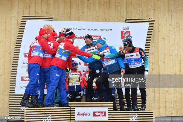 Second placed Russian team Andrey Larkov Alexander Bolshunov Alexander Bessmertnykh and Sergey Ustiugov shake hands with third placed French team...