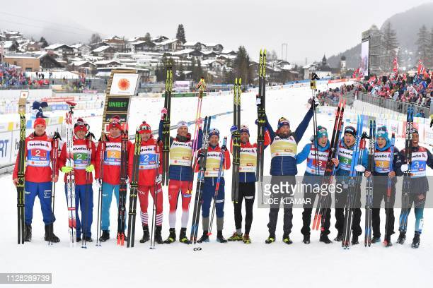 Second placed Russian team winning Norway's team and third placed French team pose after the Men's cross country skiing relay 4x10km event at the FIS...