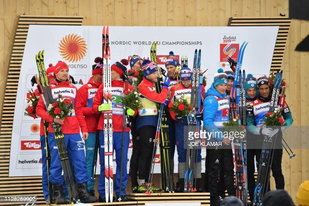 Second placed Russian team winning Norway's team and third placed French team celebrate on the podium after the Men's cross country skiing relay...