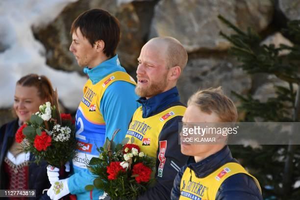 Second placed Russia's Alexander Bessmertnykh winner Norway's Martin Johnsrud Sundby and third placed Finland's Iivo Niskanen attend the flower...