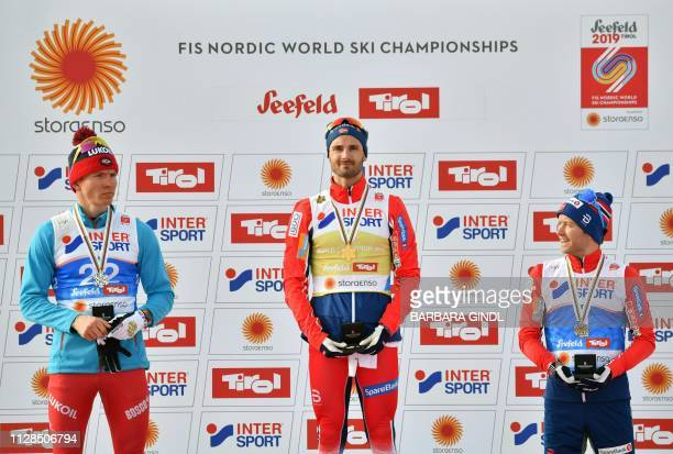 Second placed Russia's Alexander Bolshunov winner Norway's Hans Christer Holund and third placed Norway's Sjur Roethe celebrate on the podium of the...