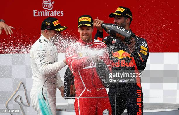 Second placed Sebastian Vettel of Germany and Ferrari celebrates on the podium in front of race winner Valtteri Bottas of Finland and Mercedes GP and...