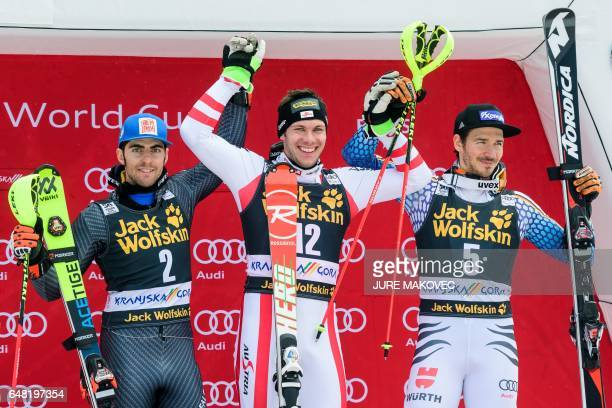 Second placed Stefano Gross of Italy winner Michael Matt of Austria and third placed Felix Neureuther of Germany celebrate on the podium after the...