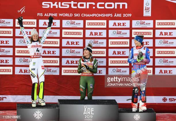 Second placed Sweden's Anna Swenn Larsson celebrates next to winner US' Mikaela Shiffrin and third placed Slovakia's Petra Vlhova during the flower...