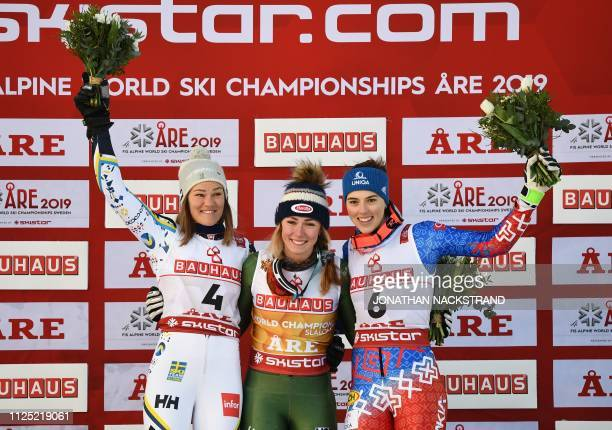 Second placed Sweden's Anna Swenn Larsson winner US' Mikaela Shiffrin and third placed Slovakia's Petra Vlhova celebrate during the flower ceremony...