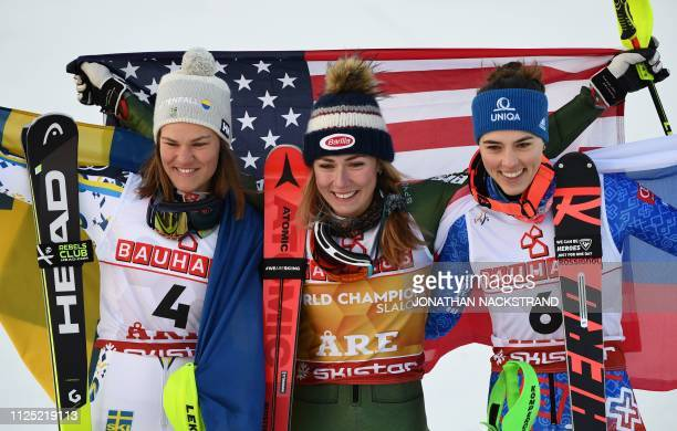 Second placed Sweden's Anna Swenn Larsson winner US' Mikaela Shiffrin and third placed Slovakia's Petra Vlhova celebrate with their flags during the...