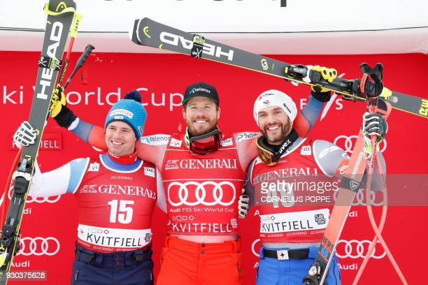 Second placed Swiss Beat Feuz winner Norwegian Kjetil Jansrud and third placed French Brice Roger celebrate after the Men's SuperG event at the FIS...