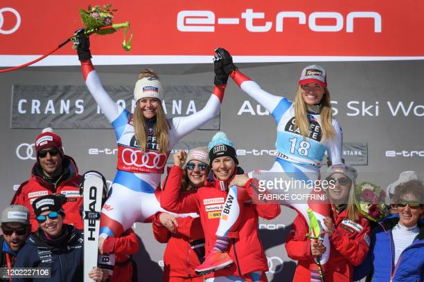 Second placed Switzerland's Corinne Suter and winner Switzerland's Lara Gut-Behrami celebrate with teammates during the podium ceremony after...
