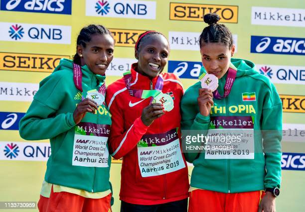 Second placed Their Dida from Ethiopia winner Helen Oberi from Kenya and third place Lete Senbet Gidey from Ethiopia pose on the podium with their...