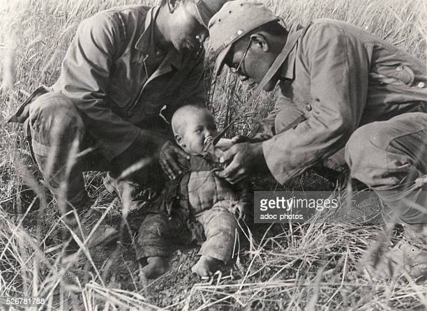 Second SinoJapanese War Young Chinese child drinking in a bottle of Japanese soldiers In June 1938