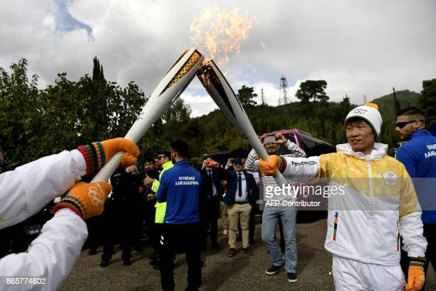 Second torchbearer for Pyeongchang 2018 former South Korean international footballer Park JiSung passes the relay of the Olympic flame near the...
