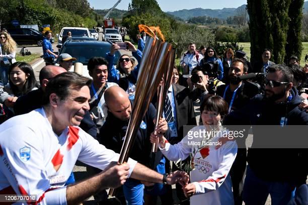 Second torchbearer Japanese former marathon runner Noguchi Mizuki passes the Olympic flame to the third torch bearer European Commissioner Margaritis...
